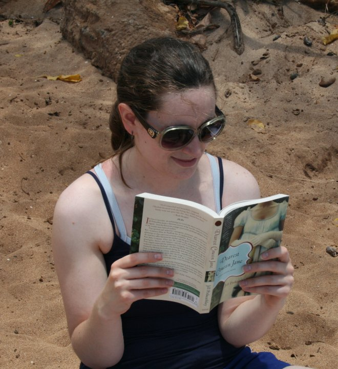 Joella reading on a beach while traveling